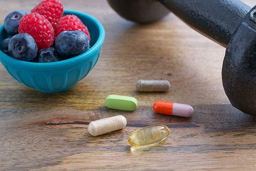 cuenco con frambuesas y arándanos,capsulas de vitaminas y mancuerna