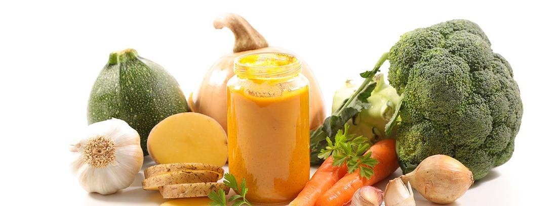 frasco de cristal con puré y diferentes verduras alrededor
