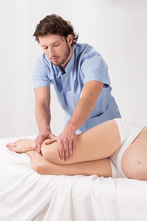 fisioterapeuta dando masajes en las piernas a mujer embarazada