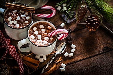 dos tazas de chocolate con bastones de caramelo en una mesa decorada de navidad