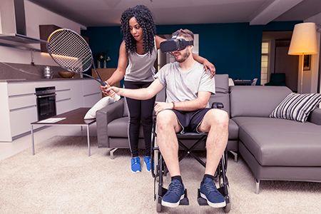 paciente en silla de ruedas con una raqueta y gafas de realidad virtual, con chica ayudándole