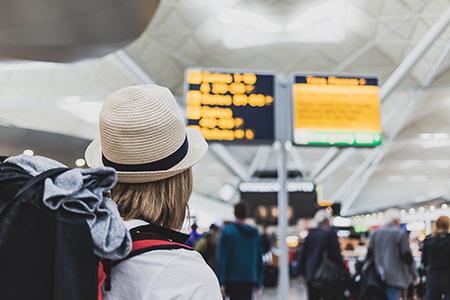 persona de espaldas con una mochila en un aeropuerto