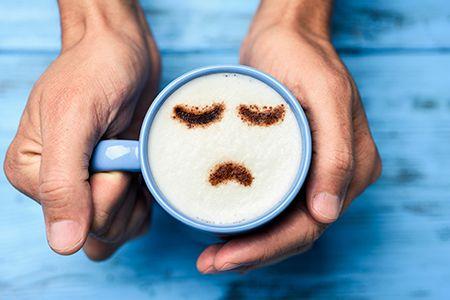 manos sujetando una taza de café y dibujado en la espuma una carita triste