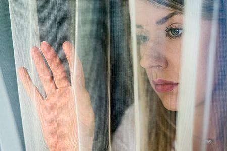 mujer con cara triste mirando a través de una cortina