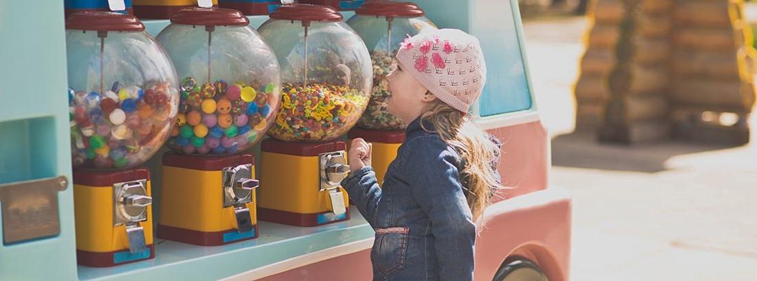 niña mirando diferentes máquinas expendedoras de chicles