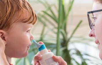 mujer realizando un lavado nasal a un niño