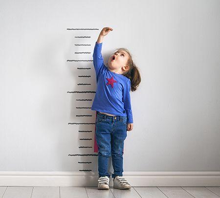 niña midiéndose la altura en una pared