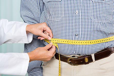 manos de mujer midiendo con un metro la cintura de un hombre
