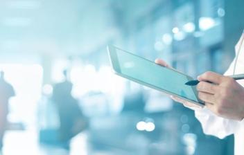 doctor en medicina con una tablet digital y fondo de un hospital