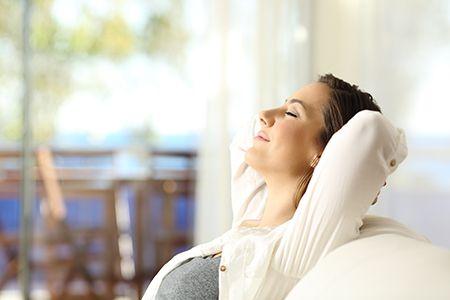 mujer relajada con los brazos detrás de la cabeza