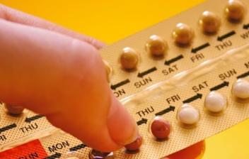 dedos sujetando una tableta de minipíldoras anticonceptivas