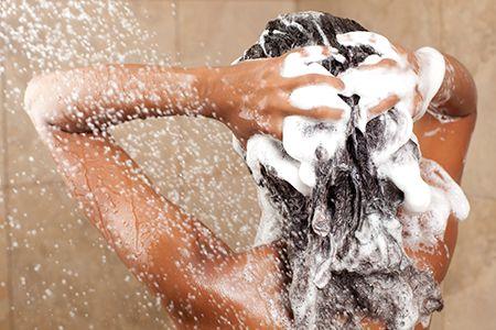 mujer lavándose el pelo con chámpu