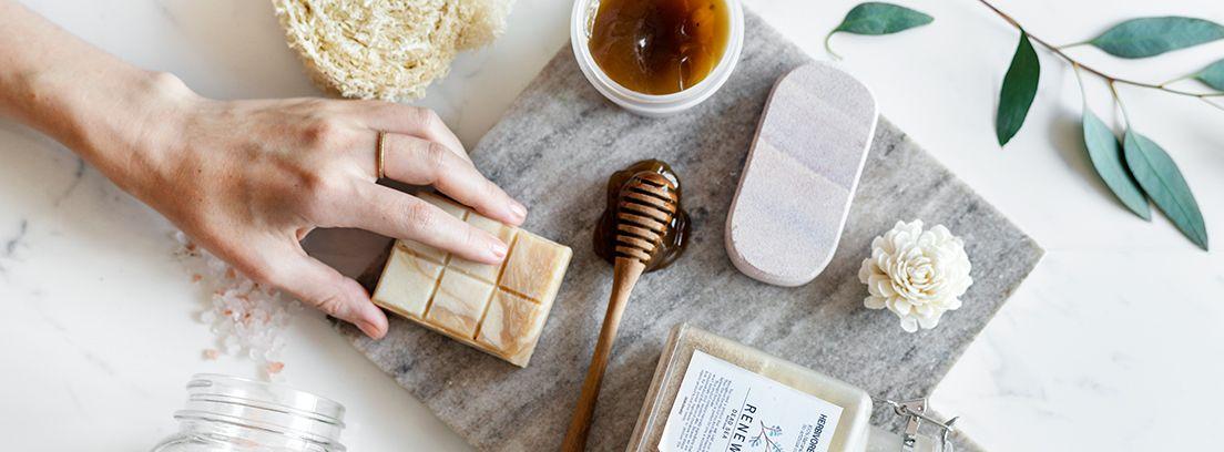 mano de mujer sujetando una pastilla de jabón y varios productos cosméticos