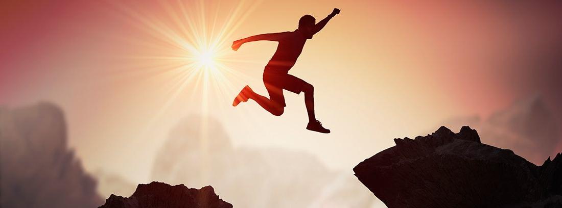 Silueta de hombre joven saltando por encima de las montañas y los acantilados al atardecer