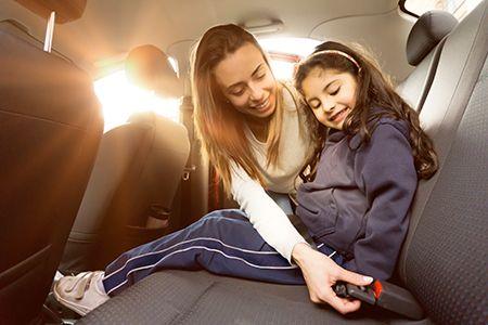 mujer poniendo el cinturón de seguridad del coche a una niña