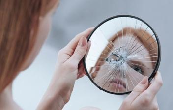 mujer con un espejo roto en las manos con su reflejo