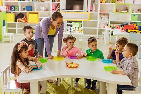 profesora enseñando a comer a niños en el colegio