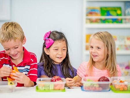 un niño y dos niñas comiendo de tupper