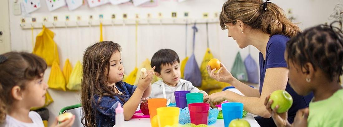 profesora en clase enseñando a comer a niños