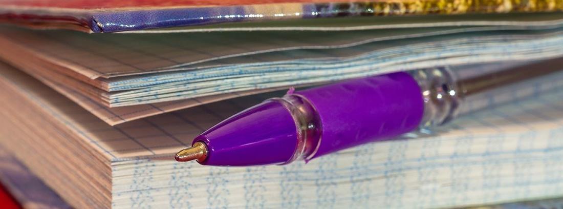 cuaderno con bolígrafo morado entre las hojas