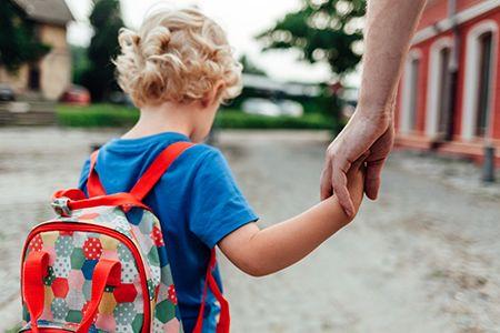 niños de espaldas con mochila de la mano de persona mayor