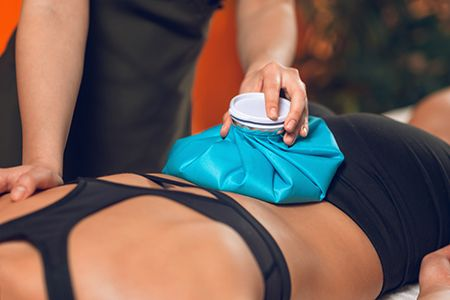 mujer tumbada con una bolsa de hielo en la espalda