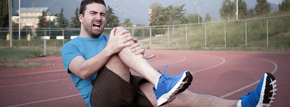 hombre deportista con gesto de dolor agarrándose la rodilla