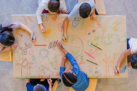 niños dibujando en una mesa de luz