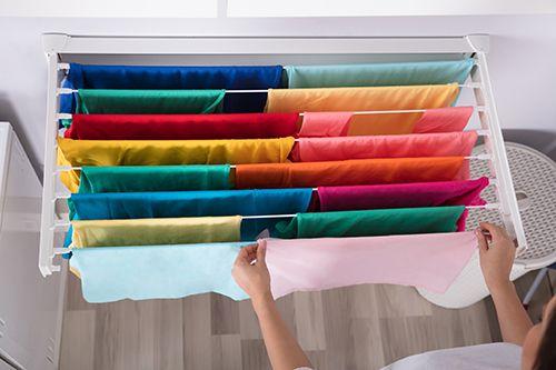 mujer tendiendo la ropa en un tendedero extensible dentro del hogar