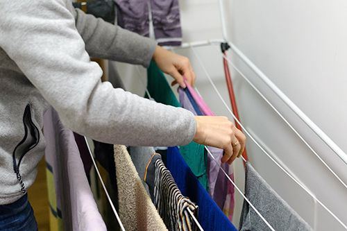 persona tendiendo la ropa en un tendedero dentro de casa