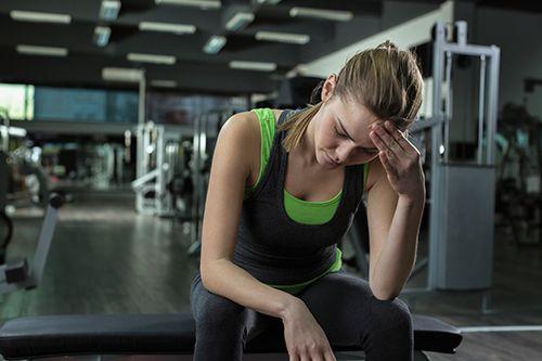 mujer deportista con la mano en la frente con gesto de dolor