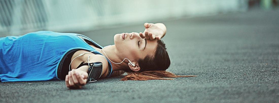 mujer deportista tumbada en el suelo por fatiga