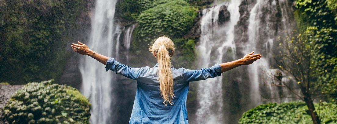 mujer rubia de espaldas contemplando una cascada en el bosque