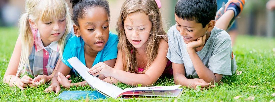 niños tumbados en el césped leyendo