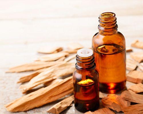 trozos de madera de sándalo y dos frascos de aceite de sándalo