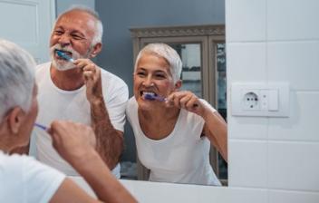 pareja de personas mayores lavándose los dientes enfrente de un espeo