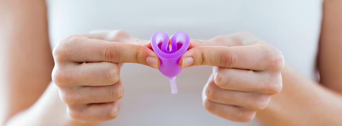 manos aplastando una copa menstrual