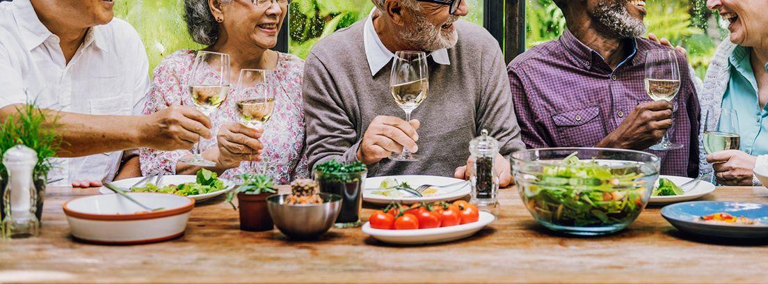 personas mayores con una copa de vino en la mano en una mesa con comida
