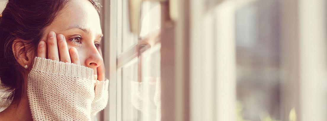 mujer mirando por la ventana con las manos sobre el rostro