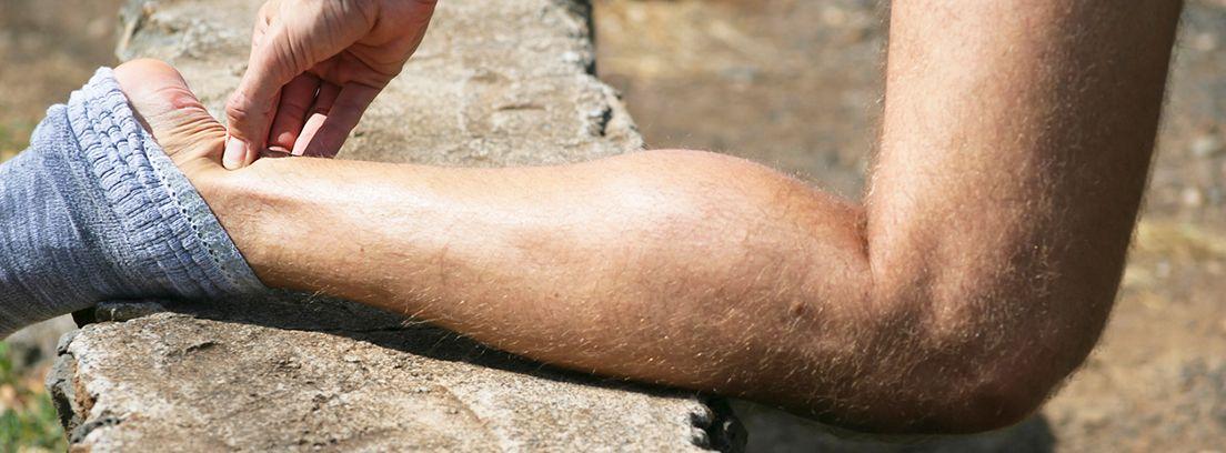 pierna de hombre presionando con la mano el tendón