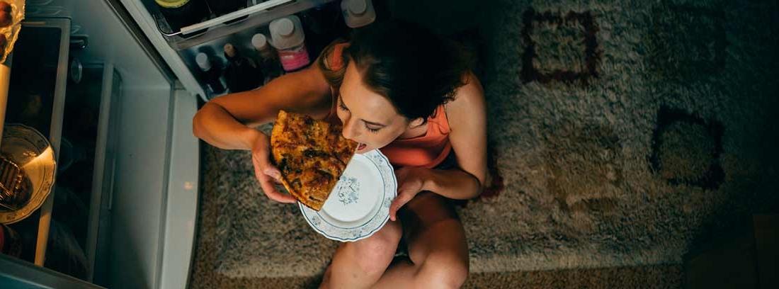 mujer comiendo pizza por la noche con la nevera abierta