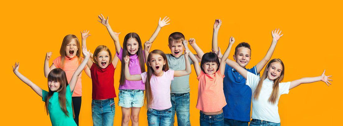niños y niñas levantando los brazos y sonriendo