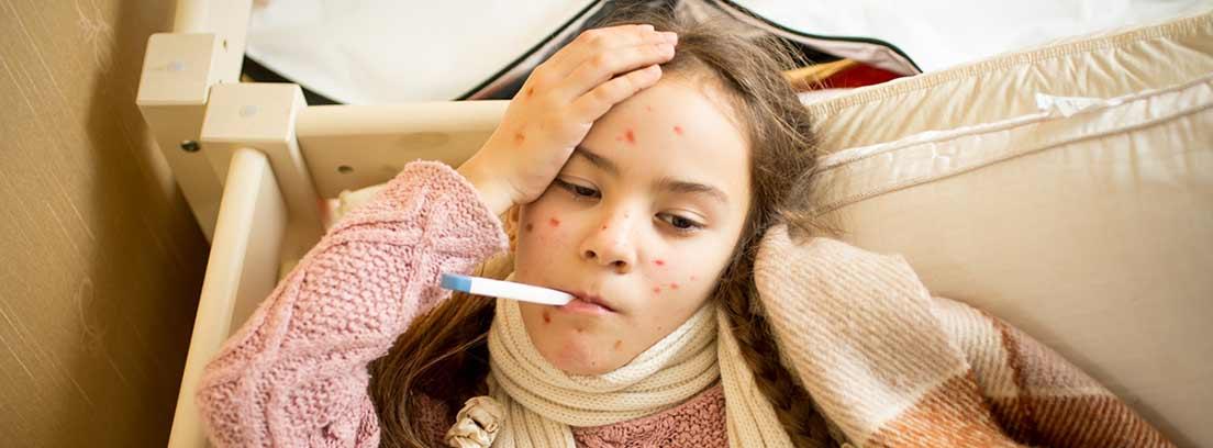 niña con sarampión tomándose la temperatura
