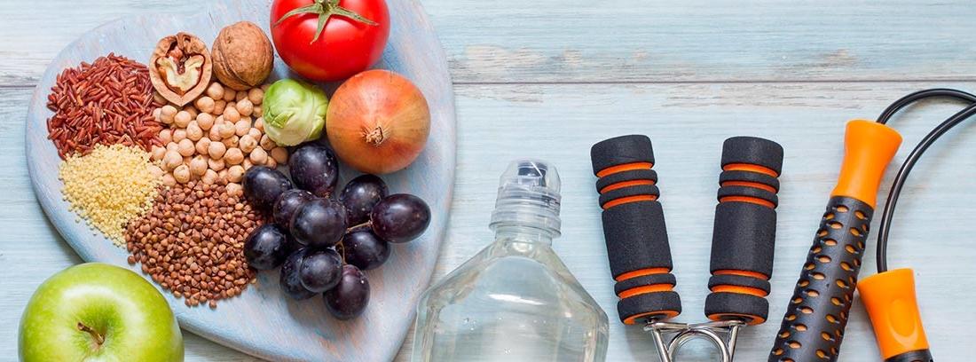 bandeja en forma de corazón con frutas y verduras, botellas de cristal y diferentes elementos para el deporte