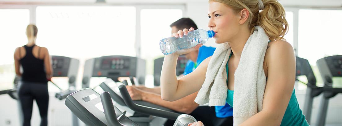 mujer deportista en cinta de correr bebiendo agua en una botella