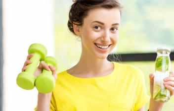 mujer con unas mancuernas en una mano y en la otra una bebida antioxidante