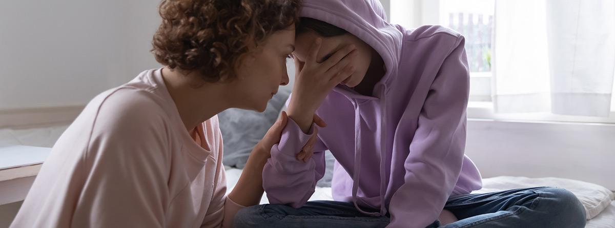 Depresión en la adolescencia: Preocupada mamá consolando a la hija adolescente deprimida llorando en casa