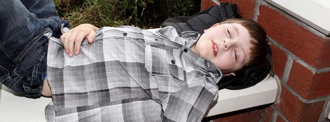 niño tumbado sobre un banco de piedra