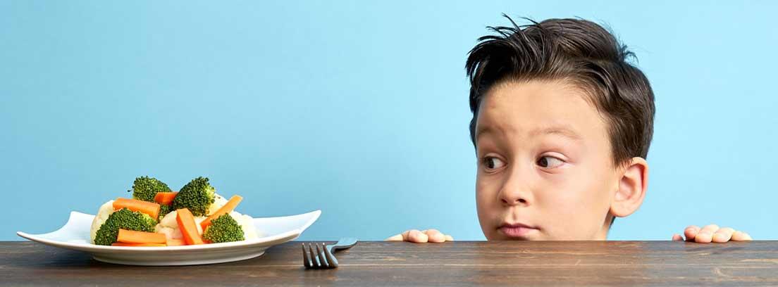 niño mirando por encima de la mesa un plato con verduras