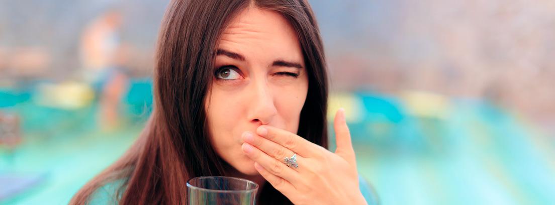 mujer quiñando un ojo con la mano en la boca por hipo